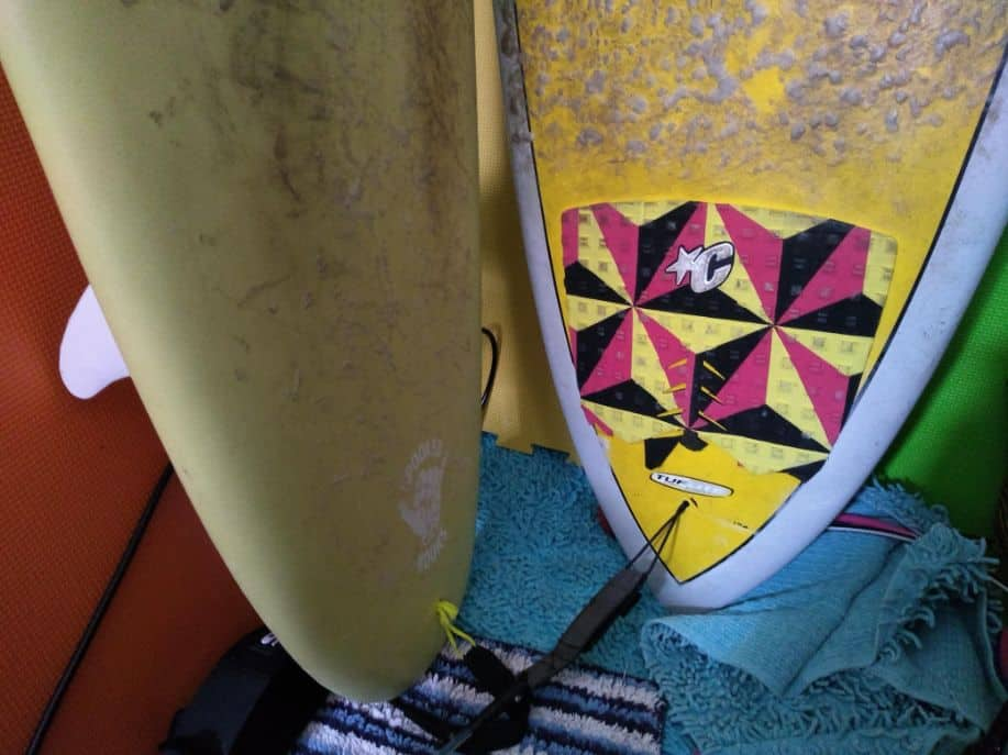 tail of two surfboards next to each other, one without a traction pad and one with a traction pad