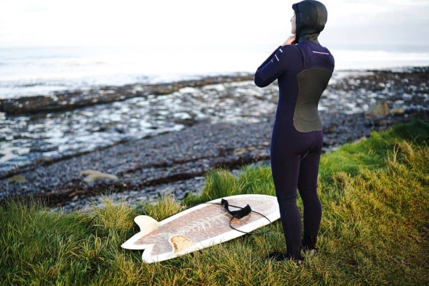 surfer in cold weather wearing a wetsuit looking out at the sea
