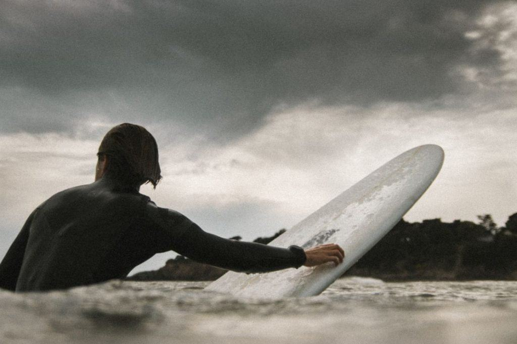 surfer sitting on a board with a grey sky to show how hard it is to balance
