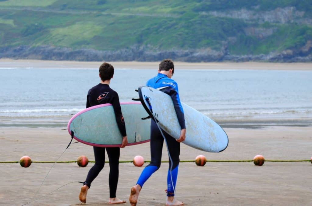 two guys carrying soft top surfboards