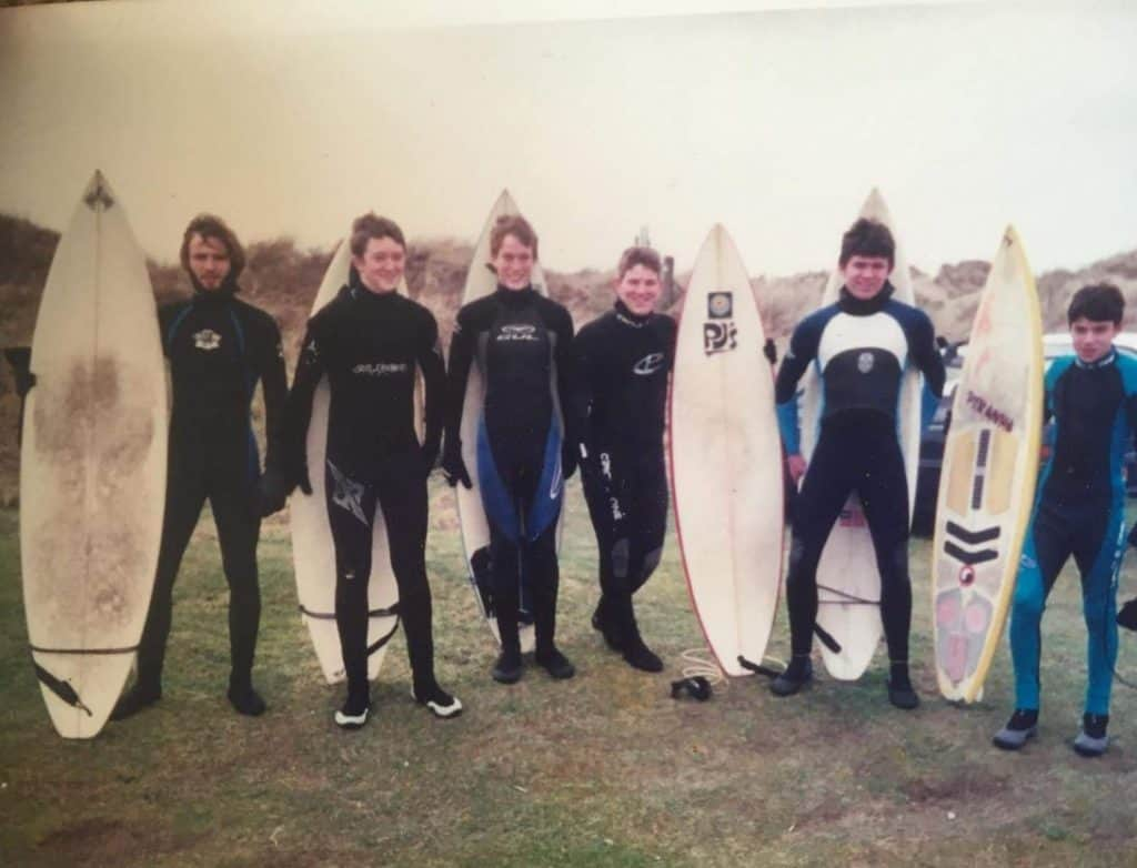 8 learner surfers with boards at the beach